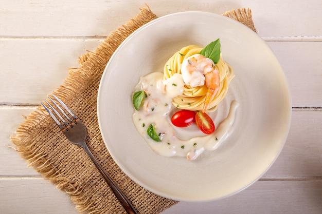 Espagueti con camarones y albahaca en un plato