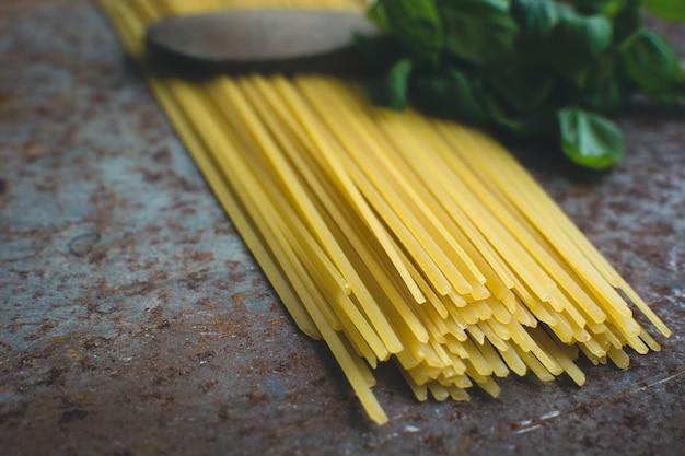 Espagueti de pasta con albahaca y cuchara de madera sobre un fondo metálico oxidado
