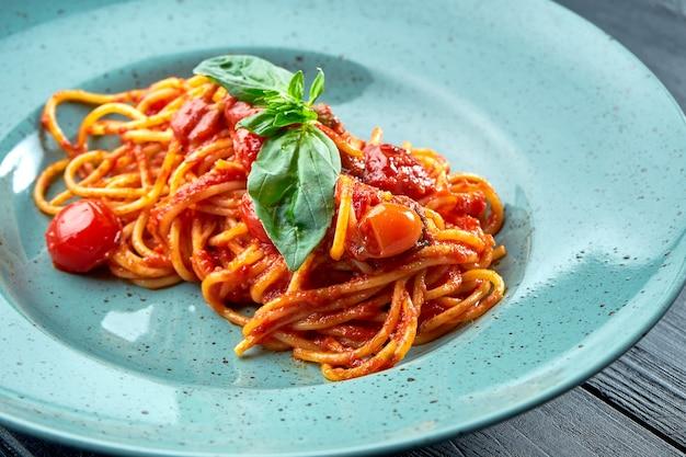 Espagueti de pasta tradicional salsa arrabbiata (con ajo rojo, pimentón y tomate) con albahaca, servido en un plato azul sobre una superficie de madera negra