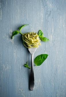 Espagueti con pesto verde y hojas de albahaca
