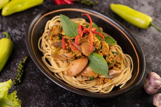 Espaguetis con almejas en un plato negro con chiles ajo y pimienta frescos.