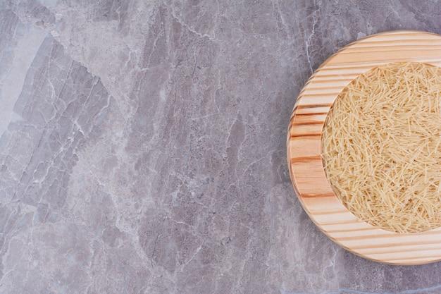 Espaguetis de arroz en bandeja de madera sobre el mármol.