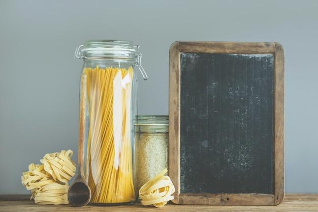 Espaguetis y arroz en frascos en la mesa de madera
