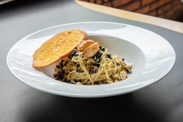 Espaguetis con baguette en plato blanco