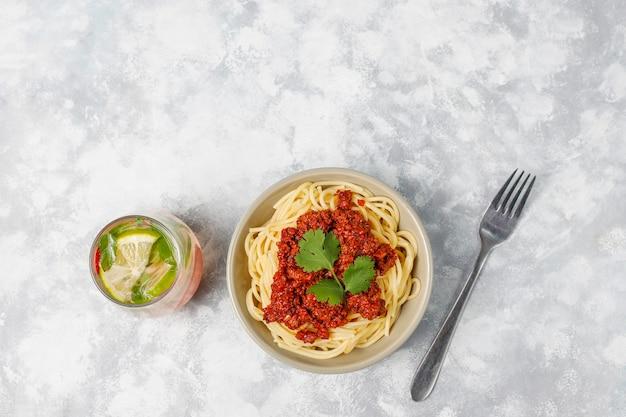 Espaguetis a la boloñesa y limonada sobre hormigón gris