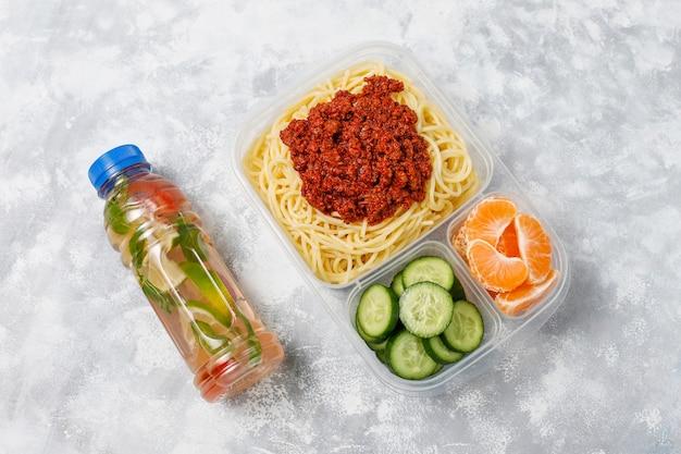 Espaguetis a la boloñesa para llevar en una lonchera de plástico con bebida de desintoxicación y una rodaja de fruta a la luz