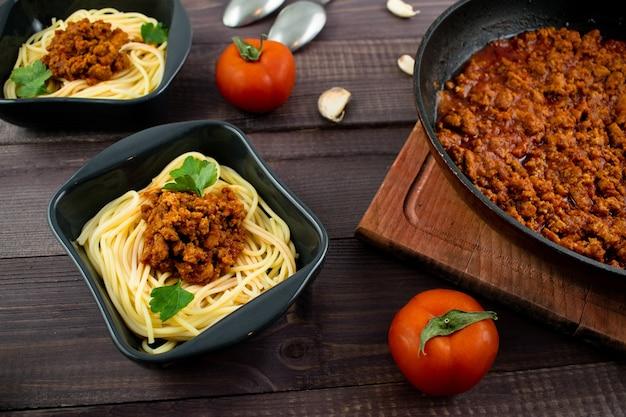 Espaguetis a la boloñesa en un plato de madera oscura