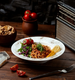 Espaguetis a la boloñesa con rodajas de tomate y limón