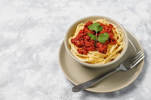 Espaguetis a la boloñesa sobre hormigón gris