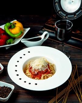 Espaguetis a la boloñesa con vino tinto sobre la mesa