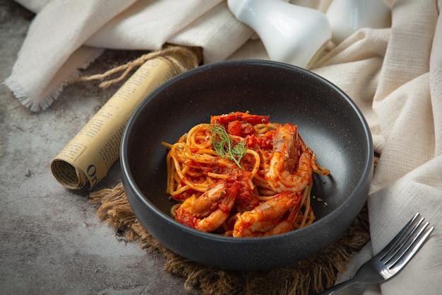 Espaguetis con camarones en salsa de tomate sobre fondo oscuro