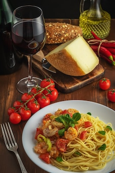 Espaguetis con camarones, tomates cherry y especias sobre fondo de madera