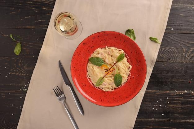 Espaguetis a la carbonara con tocino y huevo. en un plato rojo sobre una mesa de madera