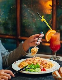 Espaguetis a la carbonara con verduras sobre la mesa