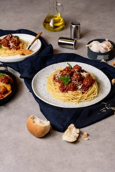 Espaguetis caseros o pasta con albóndigas y queso en salsa de tomate colocados en un plato blanco.