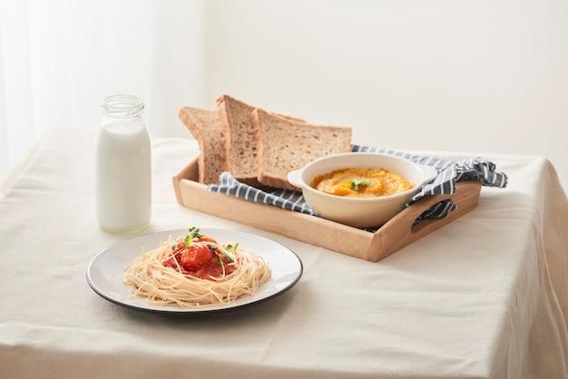 Espaguetis caseros con salsa de tomate colocados en un plato blanco sobre la mesa con puré de calabaza, leche y tostadas.