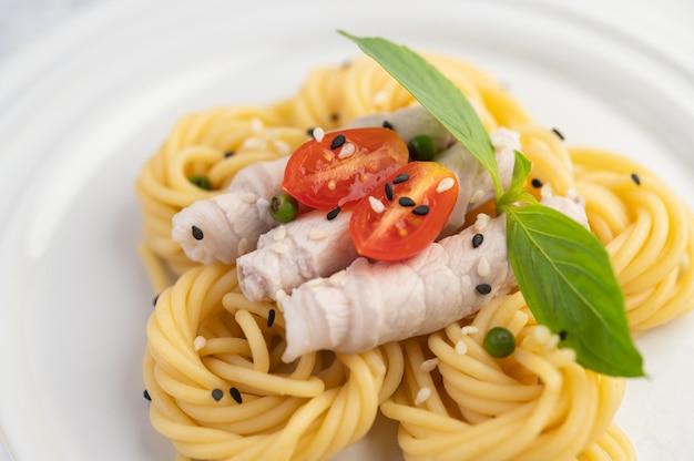 Espaguetis y cerdo salteados, bellamente dispuestos en un plato blanco.