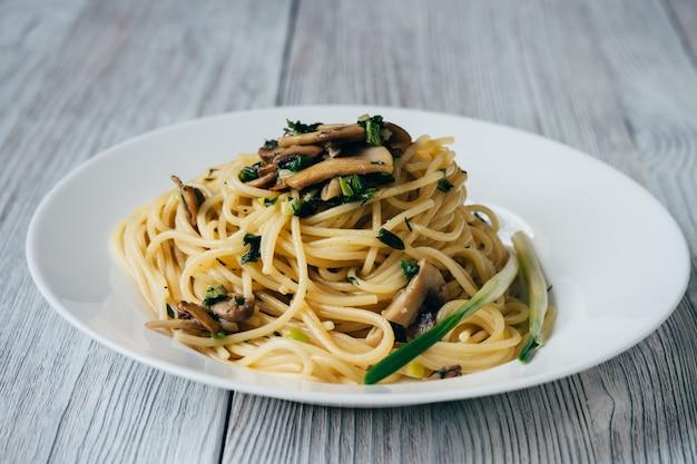 Espaguetis con champiñones y cebolla en un plato blanco