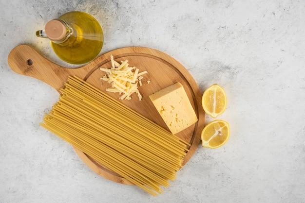 Espaguetis crudos, aceite, queso lemonnd en mesa blanca.