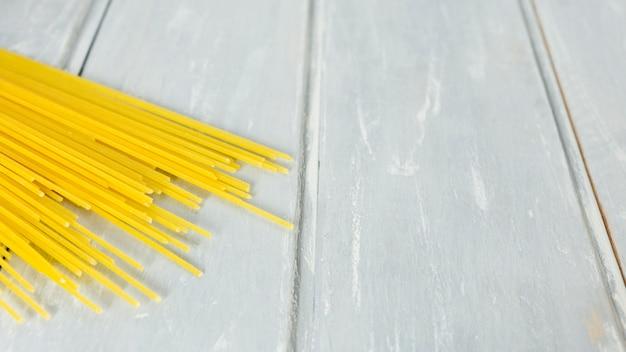 Espaguetis crudos con fondo de madera