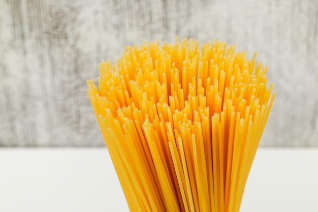 Espaguetis crudos sobre fondo blanco y grunge, vista de ángulo alto.
