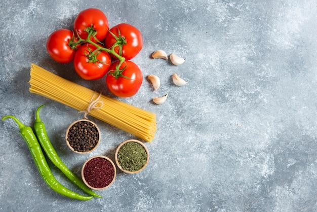 Espaguetis crudos con verduras sobre un fondo de mármol.