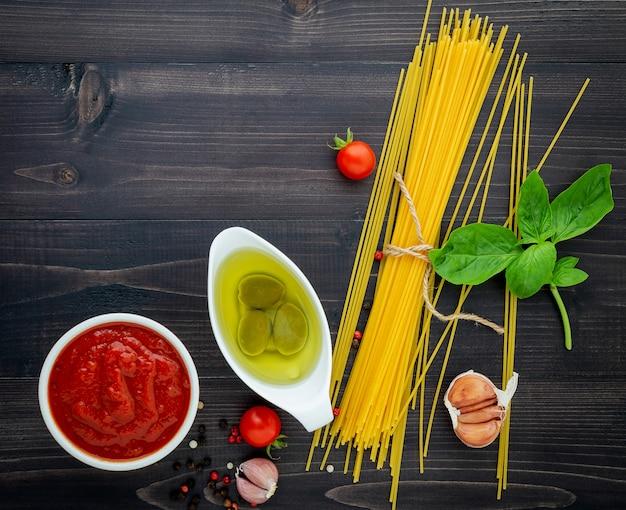 Los espaguetis finos en fondo de madera negro.