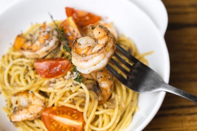 Espaguetis con gambas fritas y tomates frescos.