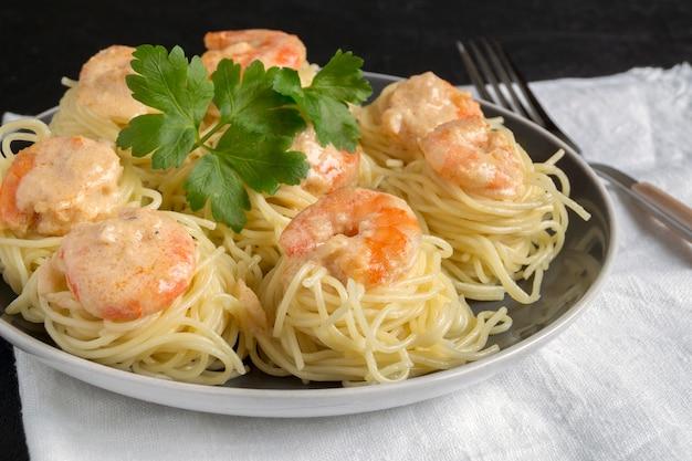 Espaguetis con gambas en salsa de nata. cocina tradicional italiana.