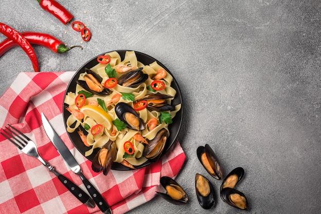 Espaguetis hechos en casa de las pastas con los mejillones, los chiles y el perejil en el fondo de piedra. comida de mar
