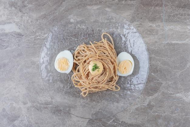 Espaguetis con huevos duros en placa de vidrio.