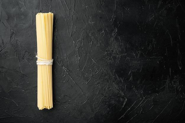 Espaguetis integrales, pasta seca sin cocer larga amarilla, sobre mesa de piedra negra, vista superior plana, con espacio de copia