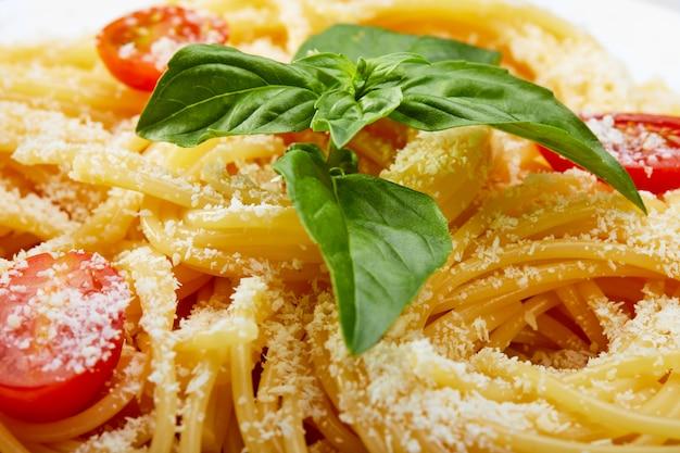 Espaguetis italianos con tomates cherry, albahaca y parmesano en un plato blanco. primer plano, enfoque selectivo