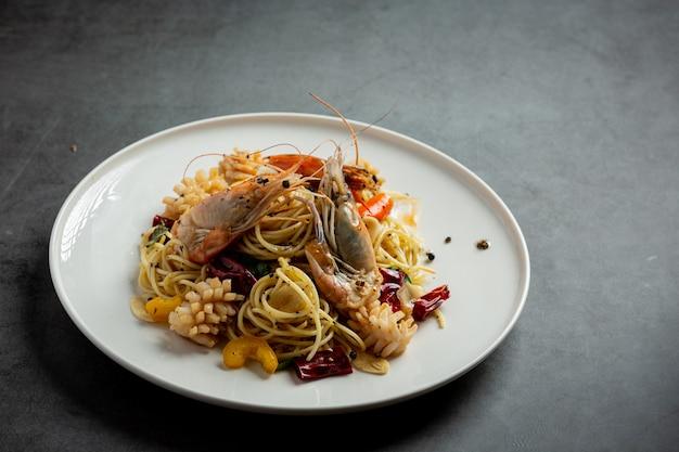 Espaguetis con mariscos mixtos picantes sobre fondo oscuro