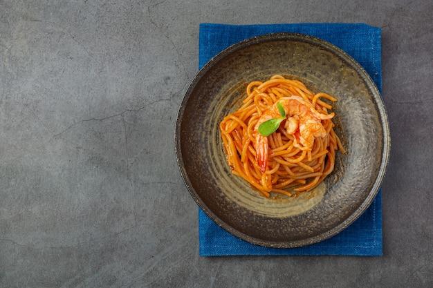 Espaguetis de mariscos con salsa de tomate decorados con hermosos ingredientes.