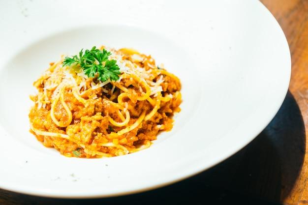 Espaguetis o pasta boloñesa en plato blanco.