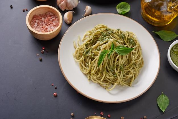 Espaguetis de pasta con calabacín, albahaca, crema y queso sobre mesa de piedra negra.