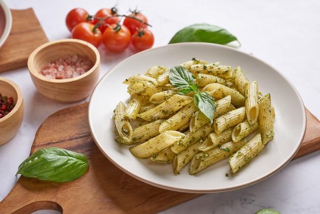 Espaguetis de pasta con calabacín, albahaca, crema y queso sobre mesa de piedra.