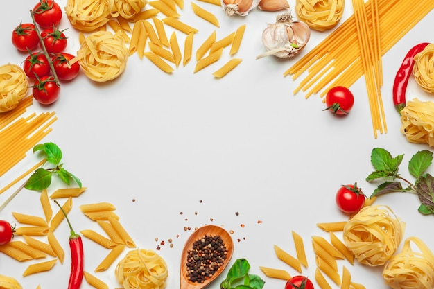 Espaguetis de pasta con ingredientes para cocinar pasta sobre un fondo blanco, vista superior.