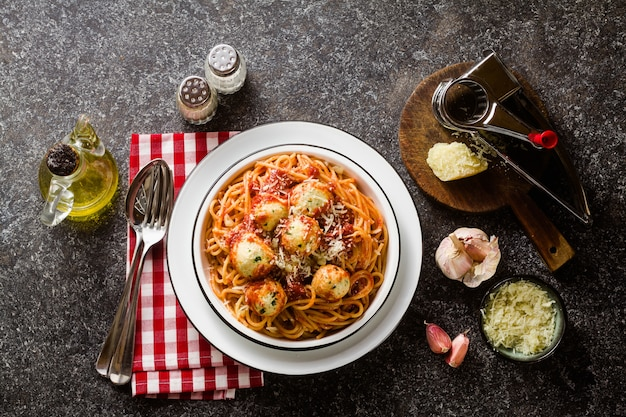 Espaguetis de pasta italiana con bolas de queso ricotta en salsa de tomate sobre la mesa con queso parmesano.