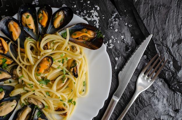 Espaguetis de pasta italiana con mejillones y perejil. concepto de comida deliciosa.