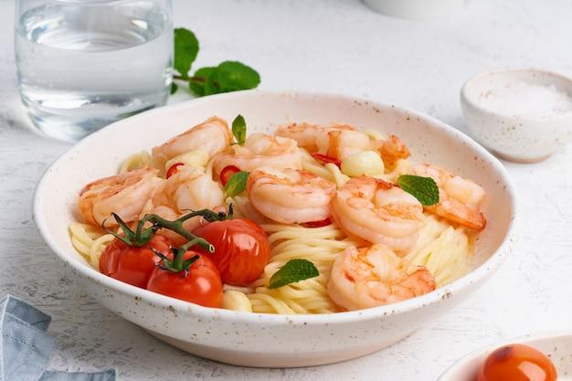Espaguetis de pasta de mariscos con camarones fritos, salsa bechamel, hojas de menta y tomates en mesa blanca
