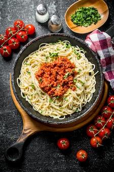 Espaguetis de pasta con salsa boloñesa en sartén con tomates, servilleta y verduras picadas en un bol. en rústico