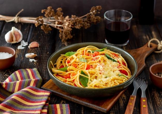 Espaguetis de pasta con tomate, albahaca y queso parmesano. cocina italiana. receta. alimentación saludable.
