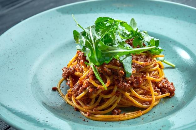 Espaguetis de pasta tradicional con carne picada y salsa boloñesa de tomate con rúcula, servidos en un plato azul sobre una superficie de madera negra. cocina italiana