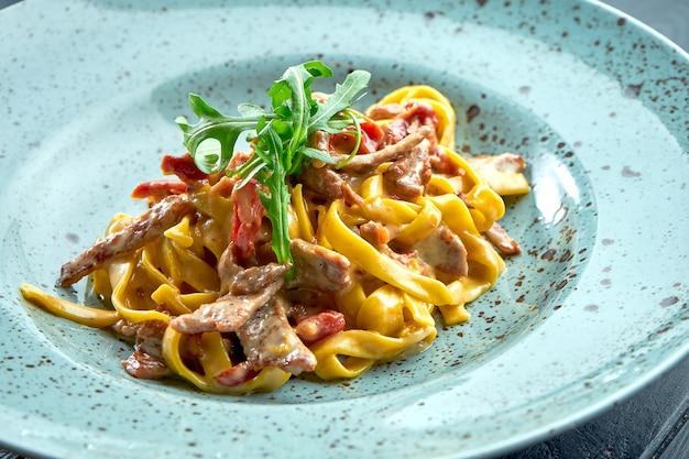 Espaguetis de pasta tradicional con salsa de crema, ternera y tomate, rúcula, servidos en un plato azul sobre una superficie de madera negra. cocina italiana