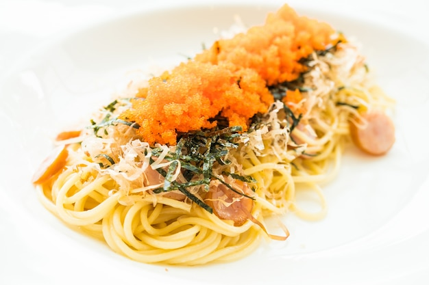 Espaguetis con salchicha, huevo de camarón, algas, calamar seco en la parte superior