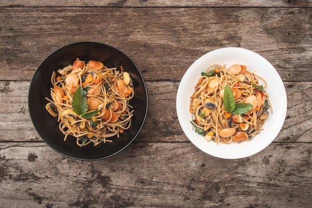 Espaguetis de salchicha picante casera con albahaca en el plato de la mesa de madera, estilo tailandés