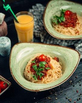 Espaguetis en salsa boloñesa, hierbas y tomate en un plato verde y jugo de naranja alrededor.