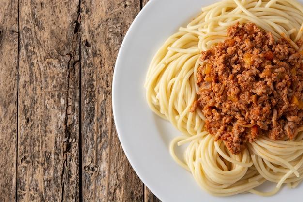 Espaguetis con salsa boloñesa en mesa de madera